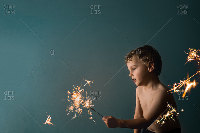 Young boy sitting holding and staring at lit sparklers.
