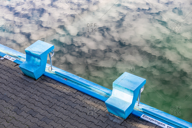 Blue diving platforms on edge of swimming pool