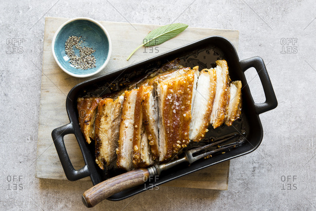 Overhead view of a sliced pork roast in roasting pan