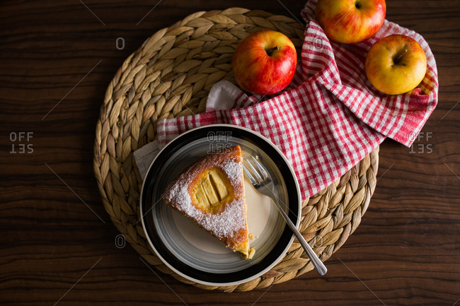 Overhead view of a slice of apple pie and fresh apples