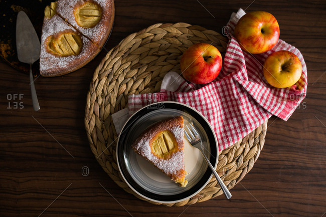 Slice of apple pie served on plate beside fresh apples