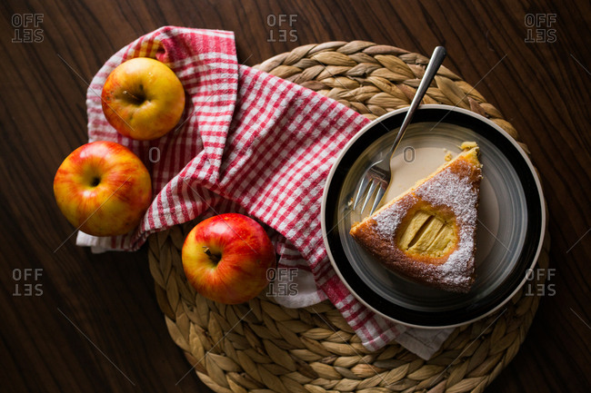 Piece of apple pie served on plate beside fresh apples