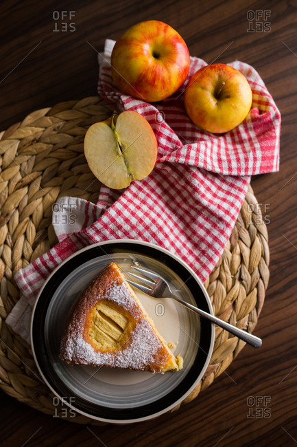 Piece of apple pie on plate beside fresh apples