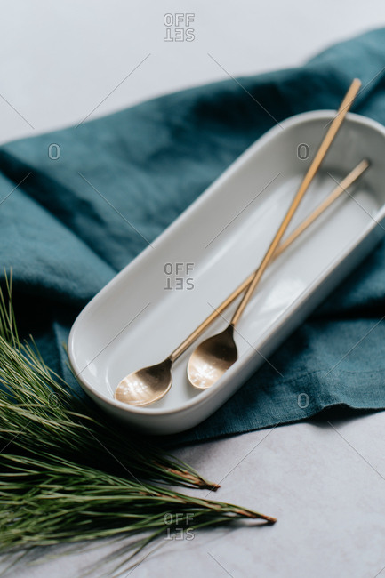 Close up of cocktail spoons in a white dish and blue cloth