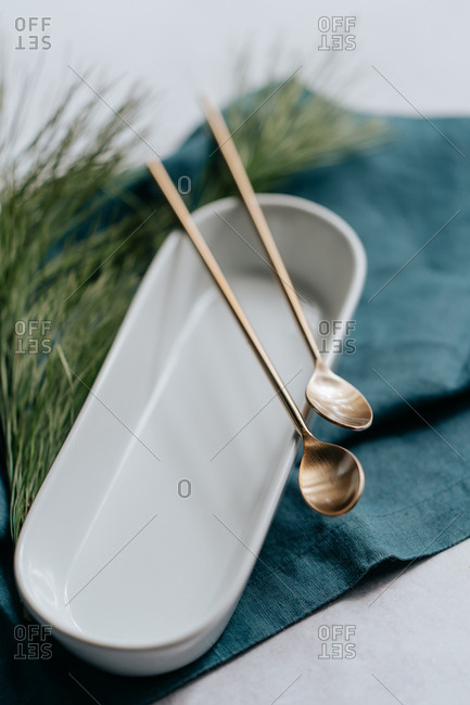 Detail of cocktail spoons in a white dish and blue cloth