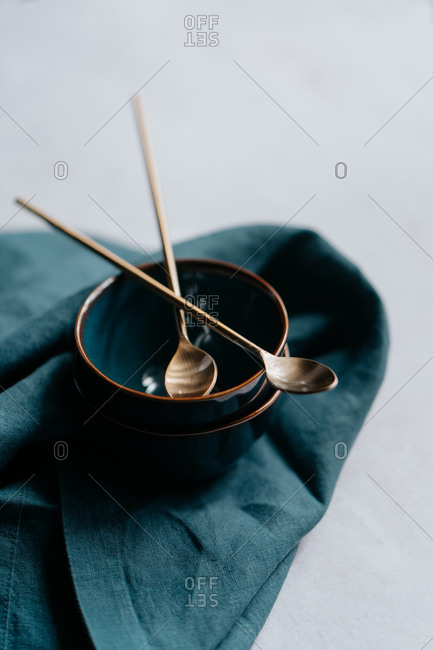 Golden cocktail spoons on top of blue bowls and cloth