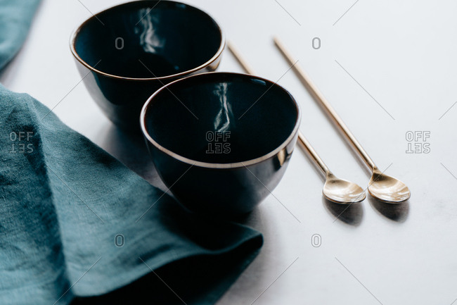 Golden cocktail spoons beside blue bowls and cloth