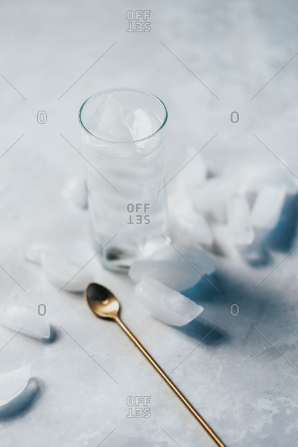 Tall glass of water with refreshing ice and cocktail spoon