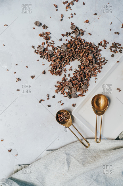 Chocolate chips and cacao nibs on light surface with gold measuring spoons