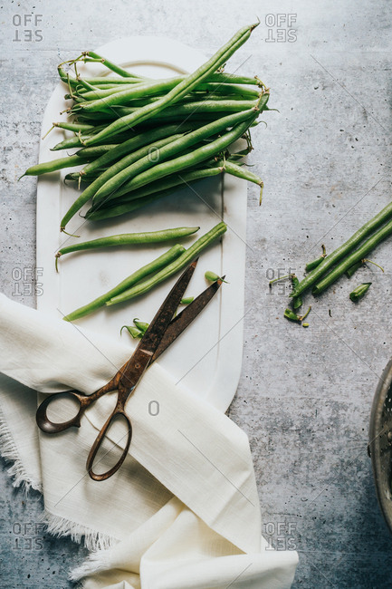 Green beans being prepared on white plate