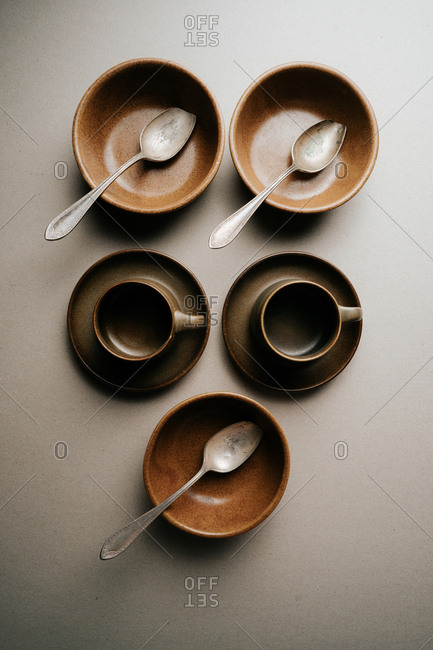 Brown mugs, saucers and bowls on light background