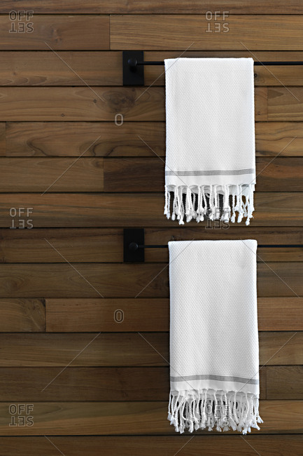 Two towels hanging on wooden wall in a hotel bathroom