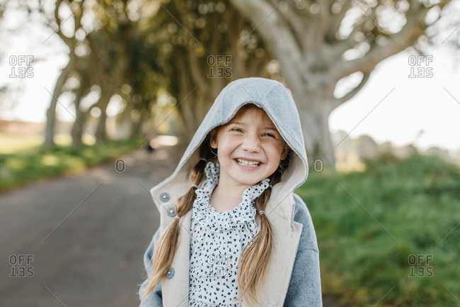 Portrait of smiling girl with pigtails on a tree-lined road