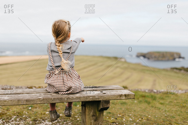 Girl sitting on wooden bench pointing out to the ocean
