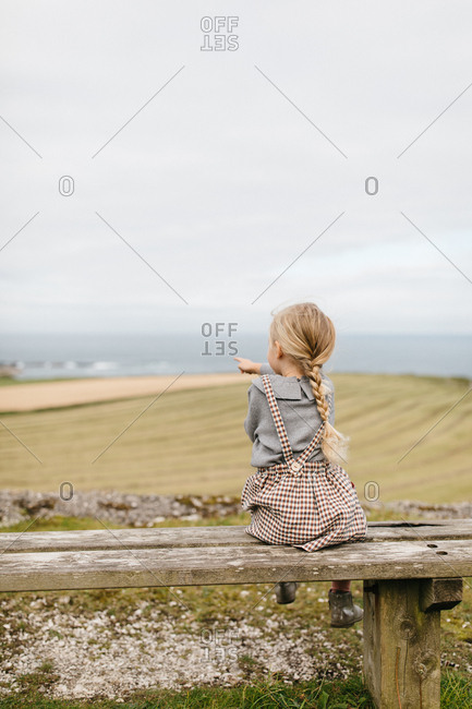 Little girl sitting on wooden bench pointing out to the ocean