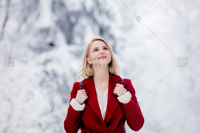 Blonde woman walking in a snowy forest