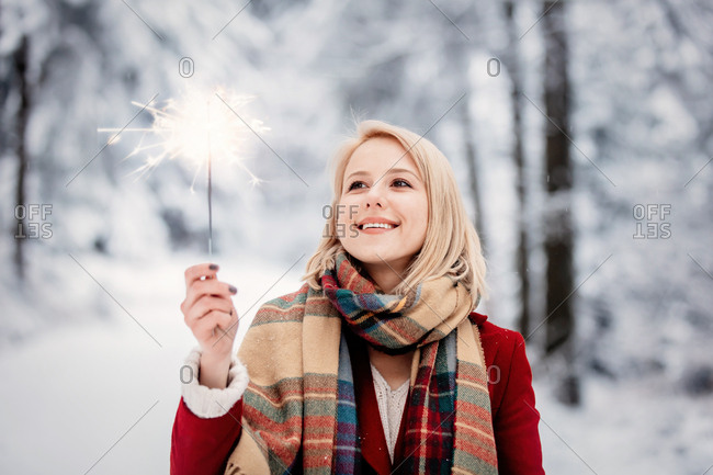 Blonde woman wearing a red coat holding a sparkler in a snowy forest