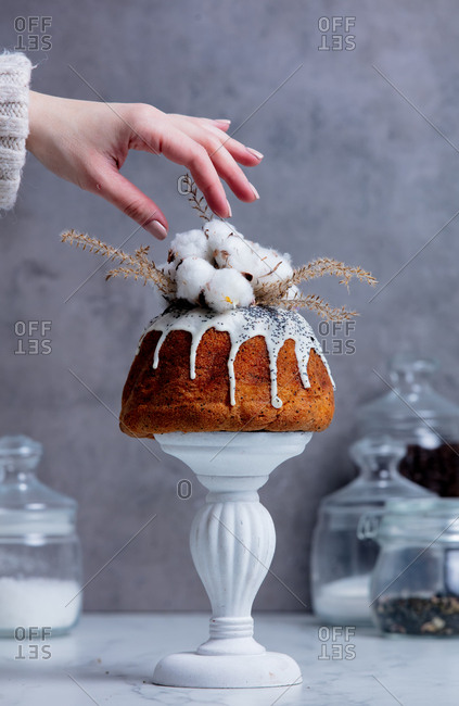 Female hand decorating cake with cotton
