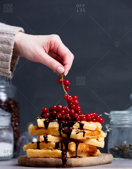 Woman places red currant on traditional waffles