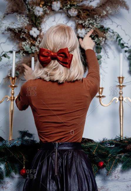 Woman with classic bow decorates a wall with Christmas wreath