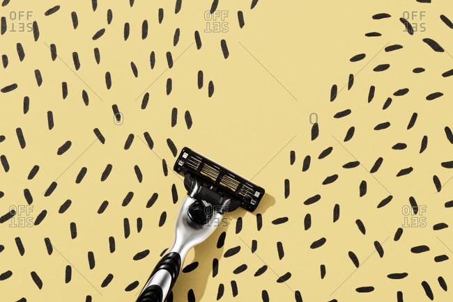 A razor shaving hair drawn on a yellow background