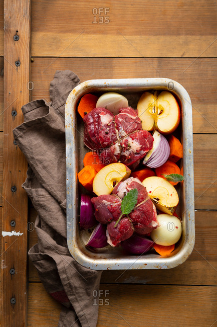 Raw meat and vegetables in baking dish