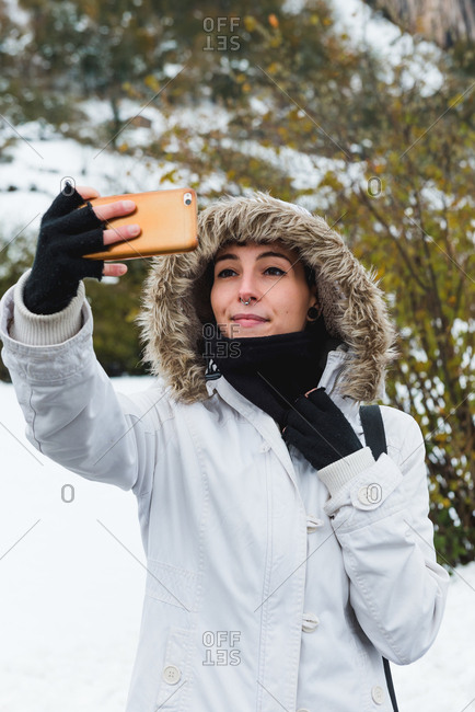 Smiling female with nose piercing wearing white winter jacket with hood and black arm warmers taking selfie with mobile phone while standing on nature at winter with bushes on background