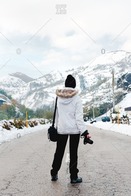 Back view of faceless person in white winter jacket with hood on head standing in middle of asphalt road at foot of mountains at snowy weather
