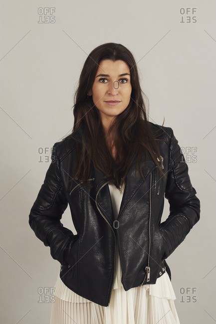 Thoughtful attractive dark haired woman in black biker jacket and looking at camera on gray background in studio