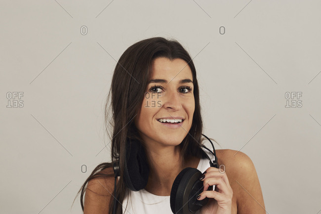 Young attractive dark haired female wearing stereo headphones and listening to music looking at camera on gray background in studio