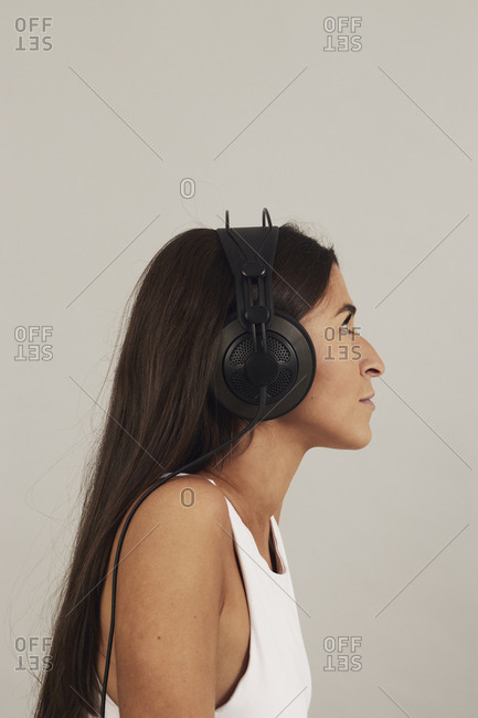 Side view of pensive young attractive dark haired female wearing stereo headphones and listening to music on gray background in studio
