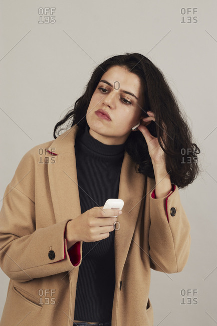 Confident youthful female brunette in beige coat placing on earbuds and listening to music on gray background in studio
