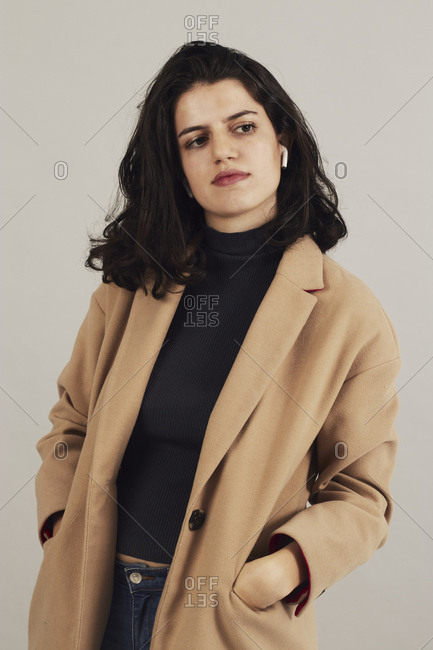 Confident youthful female brunette in beige coat with earbuds listening to music on gray background in studio