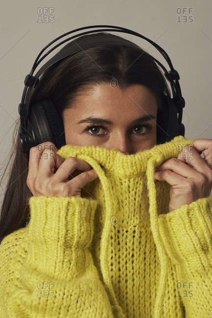 Cheerful young dark haired female in headphones looking at camera while covering face with yellow cozy sweater on gray background in studio