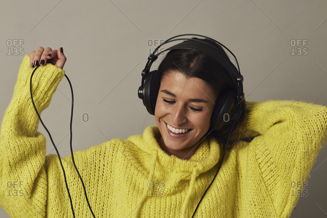 Cheerful young dark haired female in yellow cozy sweater using headphones and dancing on gray background in studio