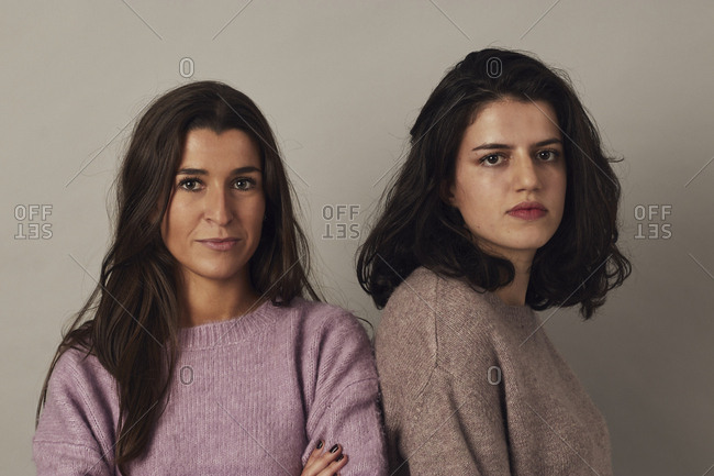 Satisfied young charming dark haired women wearing sweaters and looking at camera while standing together on gray background in studio
