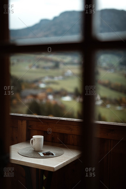 Through window view of cup of hot beverage and photos at table on wooden balcony with Dolomites mountains on blurred background