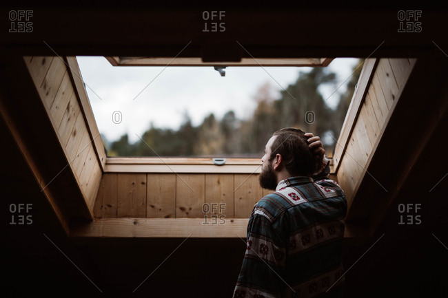 From below back view of bearded male tourist in casual shirt looking in wooden skylight delighting in nature on blurred background at Dolomites Mountains, Italy