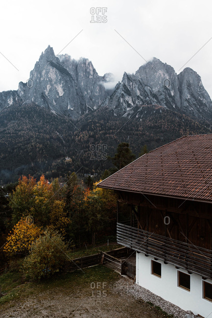 Picturesque view of building and trees in middle of valley by high mountain in Dolomites, Italy