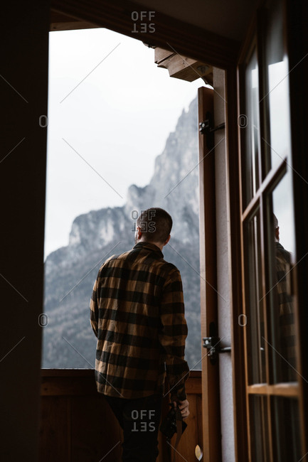 Back view of male traveler in casual plaid shirt standing in window contemplating nature at Dolomites mountains, Italy