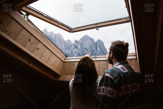 From below back view of faceless male and female travelers in casual clothing admiring landscape of Dolomites mountains at Italy from skylight
