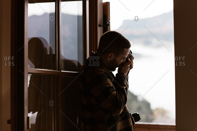 Side view of male traveler in casual plaid shirt taking photo from opened window of nature at Dolomites mountains, Italy