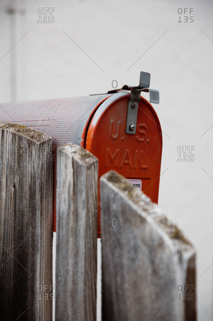 Closed red colored mailbox near a wooden fence