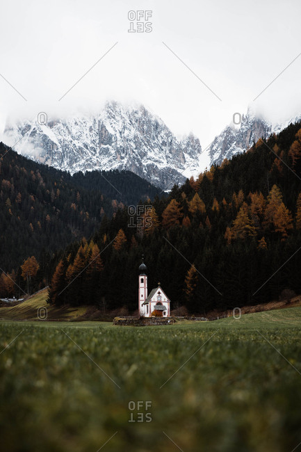 Rural small white church on slope of cliff with autumn forest sky and Dolomites mountains on background