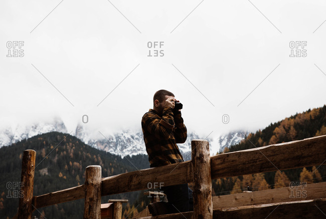 Young man leaning at a wooden fence using a photography camera in a beautiful rural mountain landscape in autumn forest in Dolomites, Italy