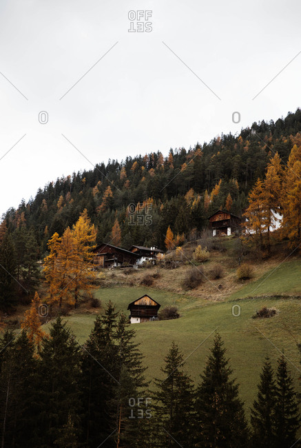 Mystery autumn landscape of countryside on shore of lake with colorful trees and cloudy sky at Dolomites mountains at Italy