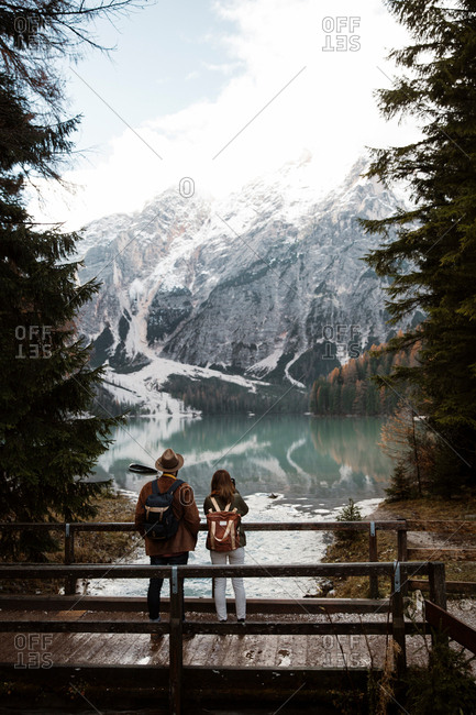 Back view of couple on vacation in casual clothing standing on wooden bridge among pine trees and enjoying in view of lake and Dolomites mountains at Italy
