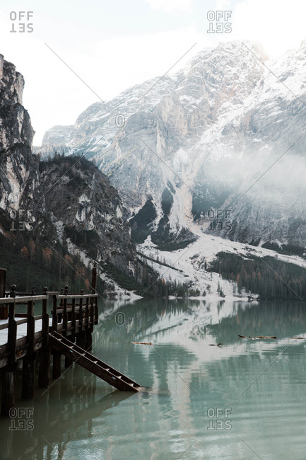 Wooden bridge pier on stilts on nebulous lake with reflection of powerful Dolomites mountains at Italy