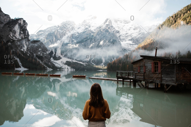 Back view of anonymous woman traveler in casual wear standing and delighting in view of wooden house on turquoise lake with foggy Dolomites mountains on background at Italy