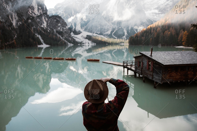 Back view of anonymous hipster man traveler in casual wear standing and delighting in view of wooden house on turquoise lake with foggy Dolomites mountains on background at Italy